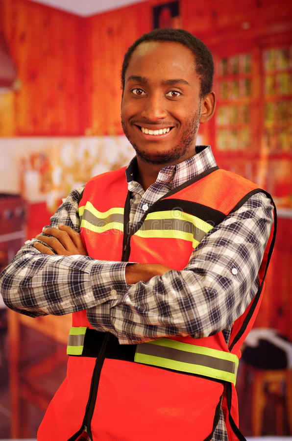 Young carpenter worker wearing square pattern flanel shirt and red safety vest, posing with arms crossed, smiling to. Camera stock image
