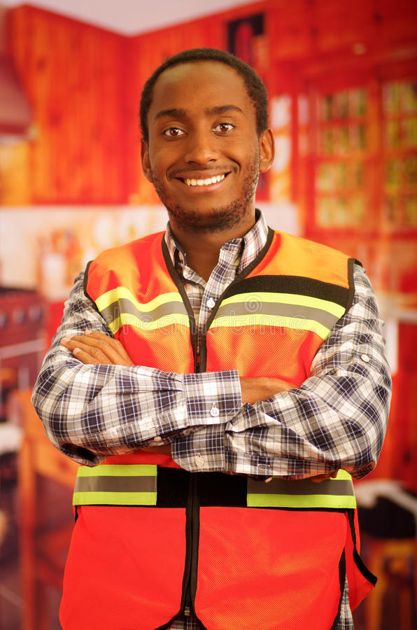 Young carpenter worker wearing square pattern flanel shirt and red safety vest, posing with arms crossed, smiling to. Camera stock photos