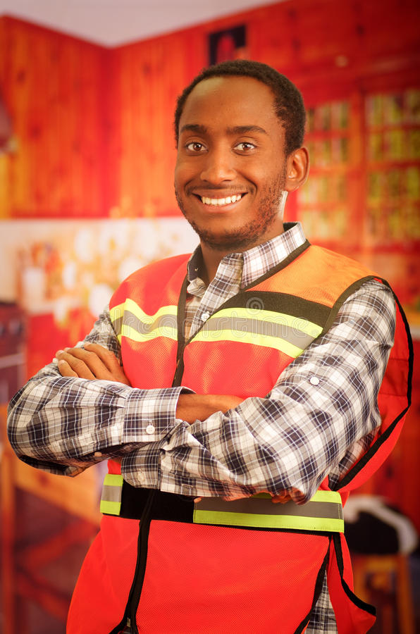 Young carpenter worker wearing square pattern flanel shirt and red safety vest, posing with arms crossed, smiling to. Camera stock images