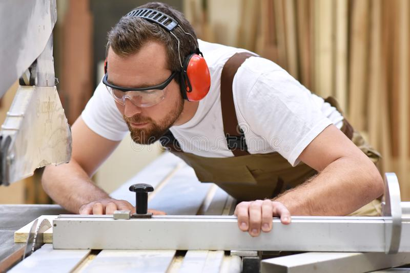 Young carpenter in working clothes works in the joinery on a san. Ding machine - working clothes with goggles and ear protection royalty free stock photos