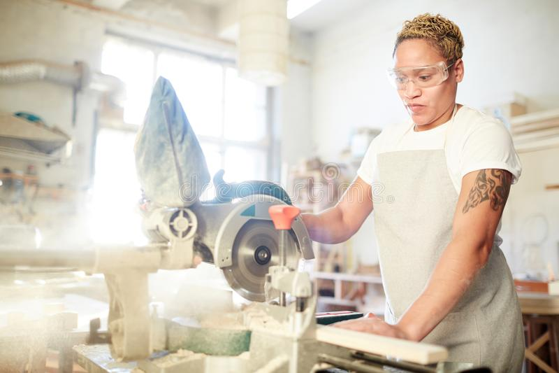 Carpenter at work. Young carpentry specialist in protective eyeglasses and apron using electric circle saw at work stock image