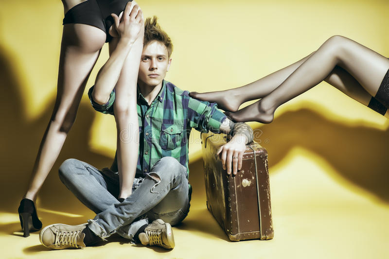 Young casanova man with suitcasen amd female legs royalty free stock photos