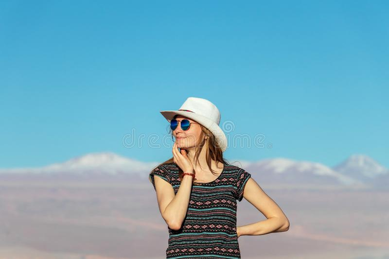 Young casual blond woman in hat and sunglasses looking away with snow covered mountains on the background. Portrait of young casual blond woman travel alone stock photo