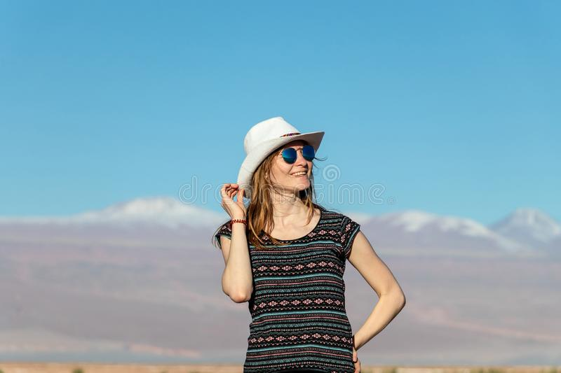 Young casual blond woman in hat and sunglasses looking away with snow covered mountains on the background. Portrait of young casual blond woman travel alone royalty free stock image