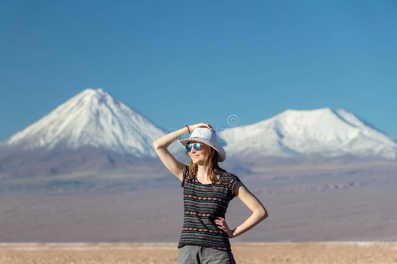 Young casual blond woman in hat and sunglasses looking away with snow covered mountains on the background. Portrait of young casual blond woman travel alone royalty free stock images
