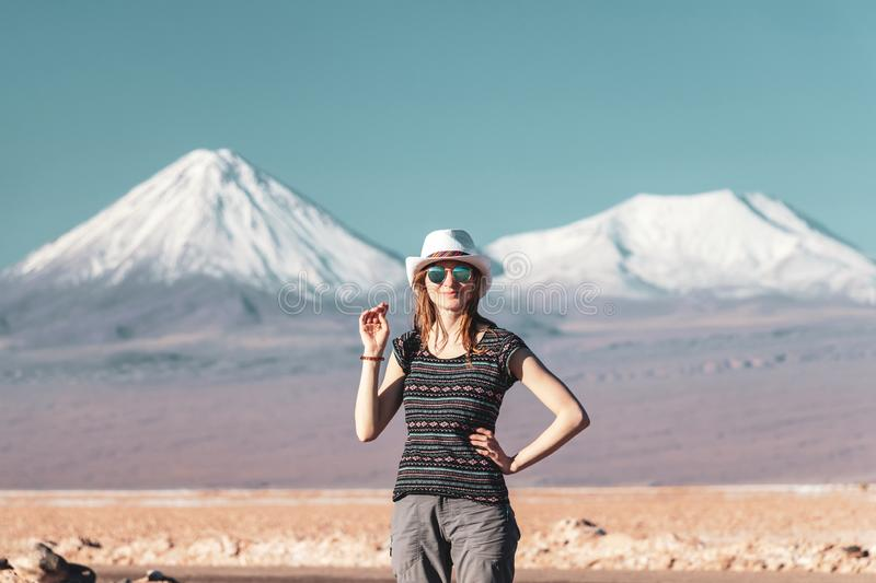 Young casual blond woman in hat and sunglasses looking at camera with snow covered mountains on the background. Young casual blond woman travel alone, caucasian stock photography