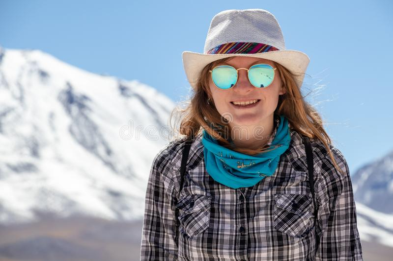Young casual blond woman in hat and sunglasses looking at camera with snow covered mountains on the background. Young casual blond woman travel alone, caucasian stock photos