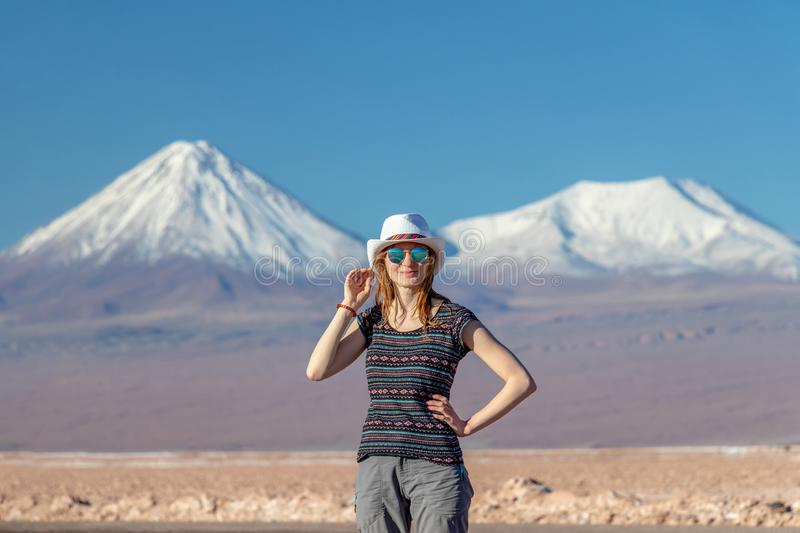 Young casual blond woman in hat and sunglasses looking at camera with snow covered mountains on the background. Young casual blond woman travel alone, caucasian royalty free stock photo