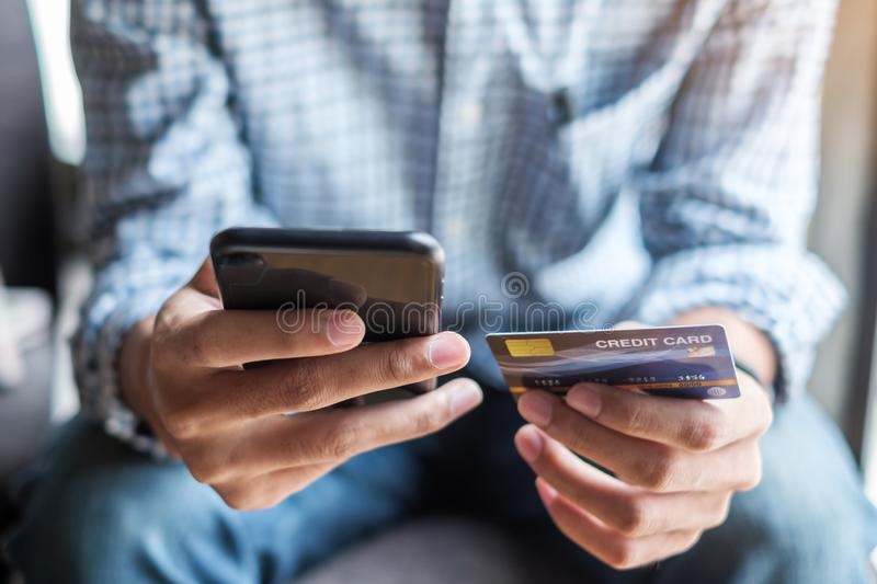 Young casual Business man holding credit card and using touchscreen smartphone for online shopping while making orders in the cafe stock photo