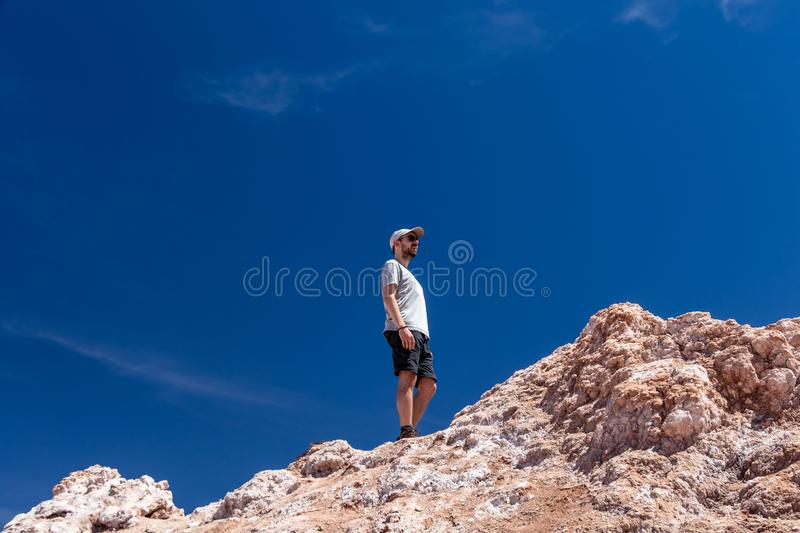 Young casual caucasian man on the top of the cliff at Valle de la Luna Moon valley, Chile. Young casual caucasian confident man on the top of the cliff at moon stock photo