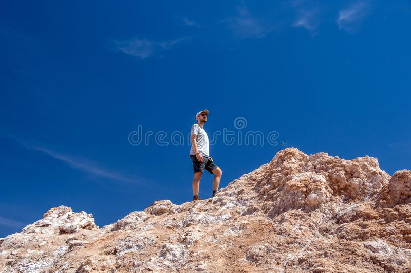 Young casual caucasian man on the top of the cliff at Valle de la Luna Moon valley, Chile. Young casual caucasian confident man on the top of the cliff at moon stock image