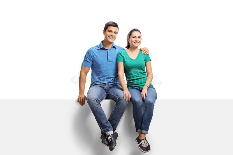 Young casual couple sitting on a panel and smiling at the camera royalty free stock photo