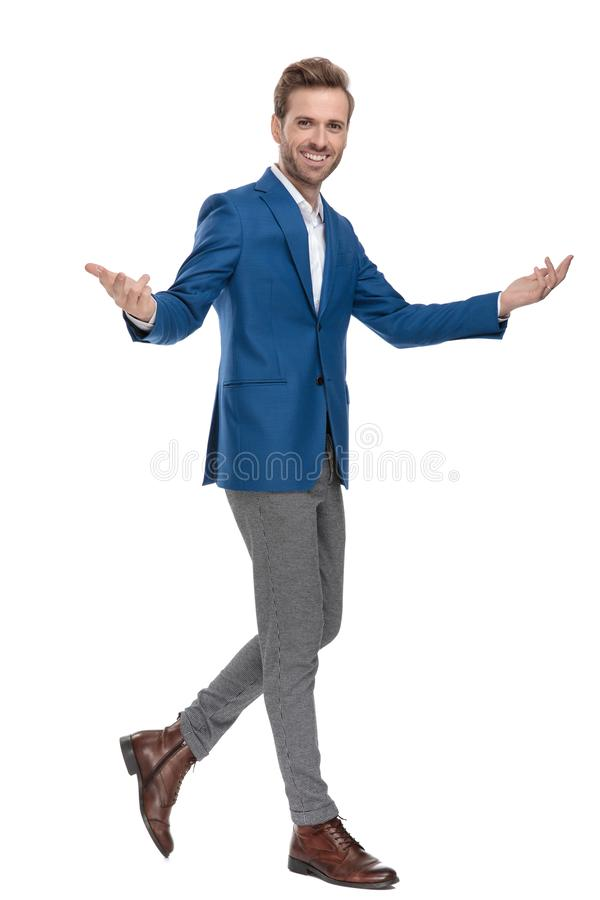 Young casual guy greeting with his arms wide open. While walking and wearing a suit on white studio background stock photos