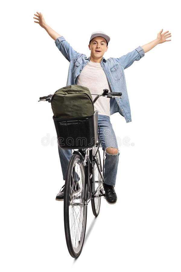 Young casual guy riding a bicycle with raised hands stock photos