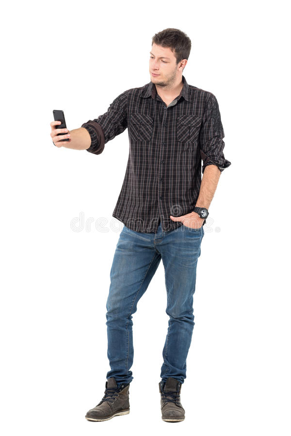 Young casual handsome man taking low angle selfie with smart phone stock photos