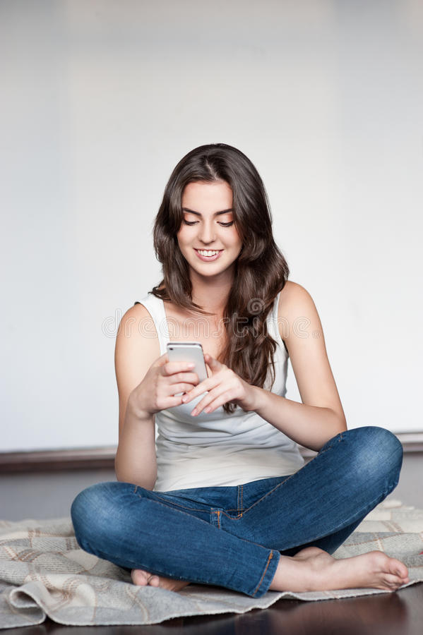 Young casual happy smiling girl with cell phone