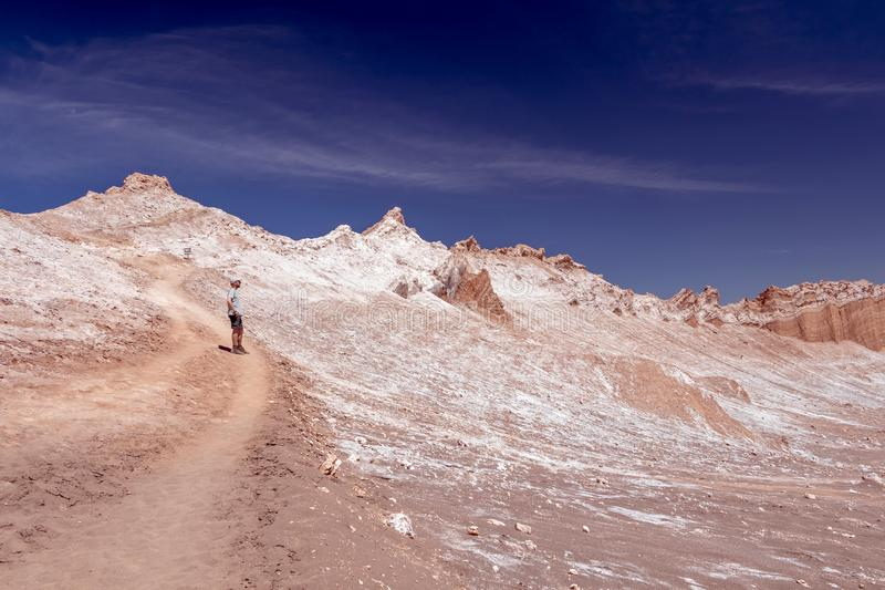 Young casual man with backpack on the path at moon like landscape of Valle de la Luna Moon valley. Chile royalty free stock photos