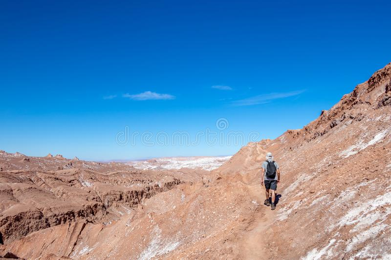 Young casual man with backpack on the path at moon like landscape of Valle de la Luna Moon valley, Chile. Travel Lifestyle hiking concept summer vacations stock photos