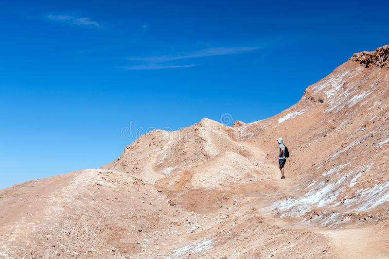 Young casual man with backpack on the path at moon like landscape of Valle de la Luna Moon valley, Chile. Travel Lifestyle hiking concept summer vacations stock images