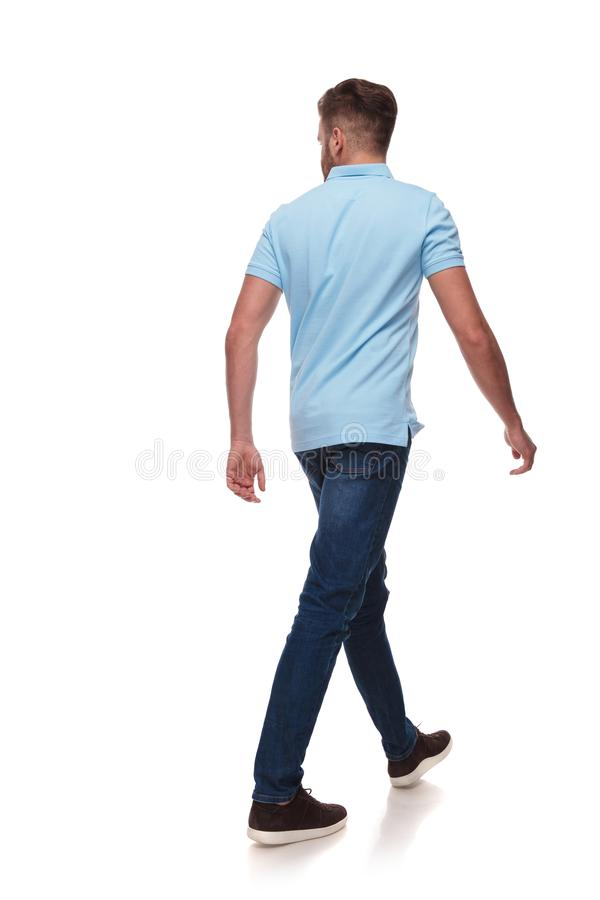 Young man in polo shirt walks and looks to side. Young casual man in blue polo shirt walks and looks to side on white background, full length picture stock photo