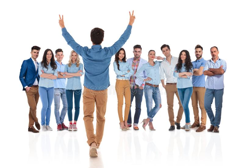 Young casual man congratulates his colleagues with hands up royalty free stock images