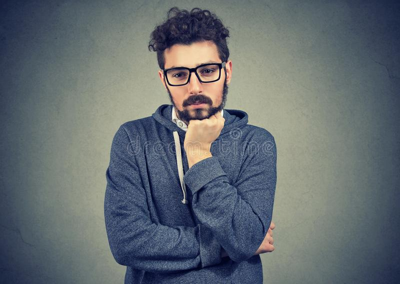 Preoccupied young man thinking thoroughly stock photo