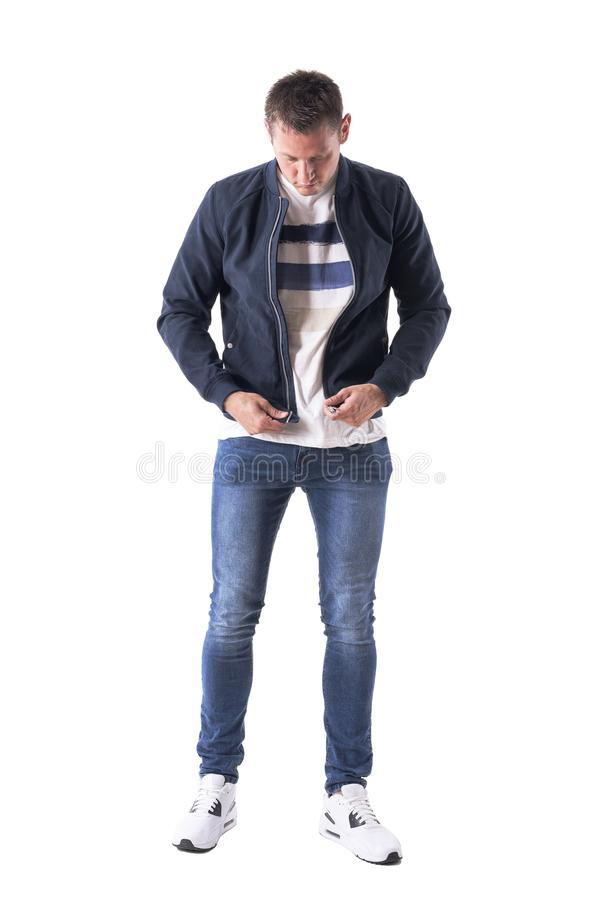 Young casual man getting dressed up holding and preparing to zip up jacket fastener. Full body isolated on white background royalty free stock photography