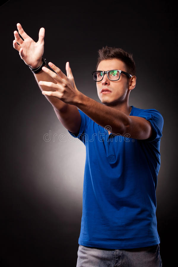 Young casual man holding his hands up stock photography