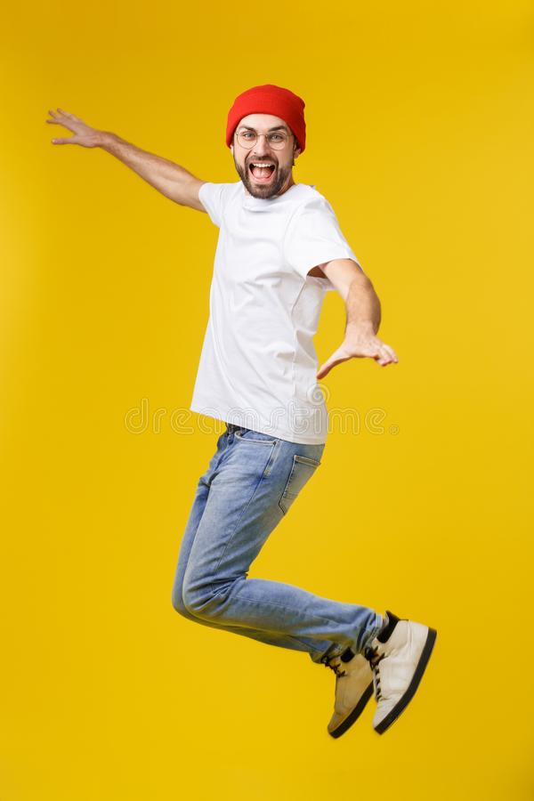 Free Young Casual Man Jumping For Joy On Yellow Gold Background Royalty Free Stock Photography - 164376157