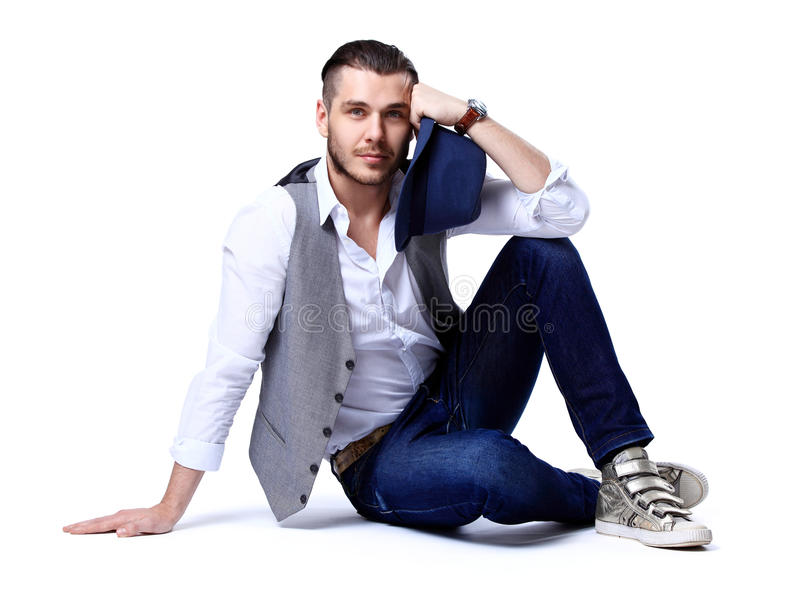 Young casual man posing on the floor and smiling stock images