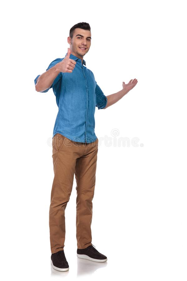 Young casual man presents to side and makes ok sign stock photo