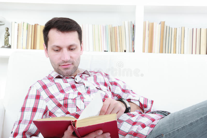 Young casual man reading a book relaxing on sofa royalty free stock photography