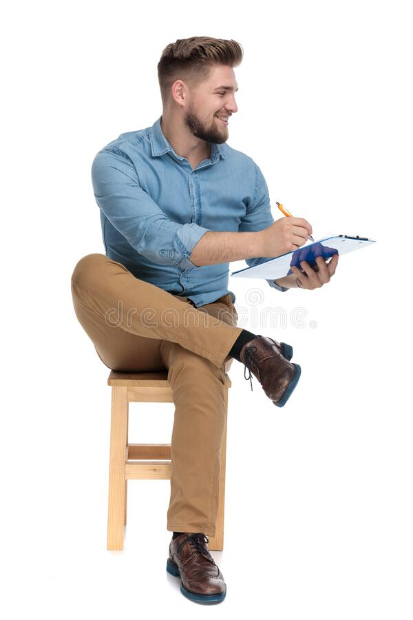 Young casual man smiling and writing on clipboard stock images