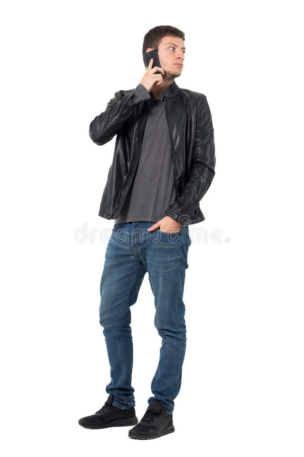 Young casual man talking on the mobile phone turn back looking behind. Full body length portrait isolated over white background stock photo