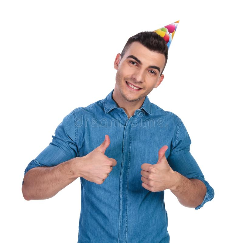 Young casual man wearing birthday hat makes ok sign. While standing on white background stock image