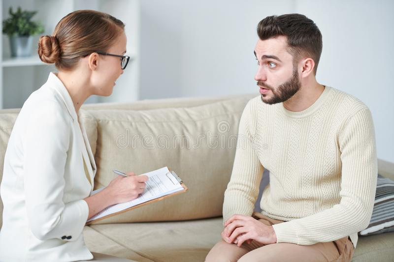 Asking for advice. Young casual men looking at counselor during discussion of his problems during individual session stock images