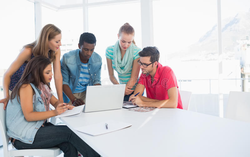 Young casual people using laptop in office royalty free stock photography