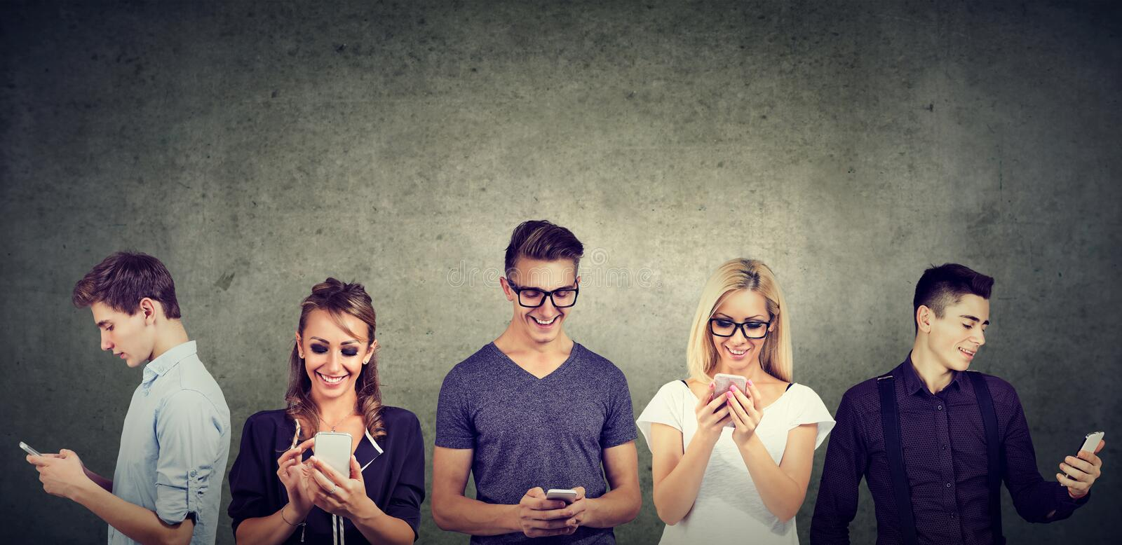 Young casual people using mobile phone standing together against concrete wall. Young people in casual clothes using mobile phone standing together against royalty free stock image