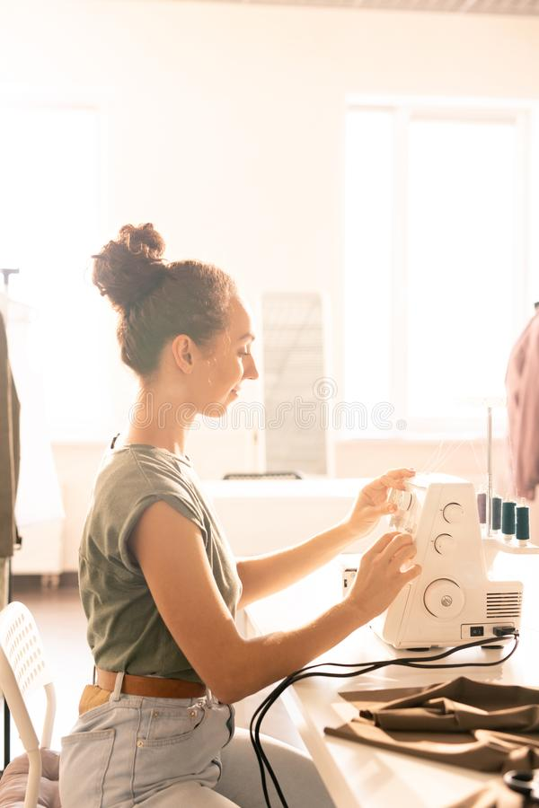 Woman sewing. Young casual seamstress sitting by table in front of sewing machine while preparing for working process royalty free stock images