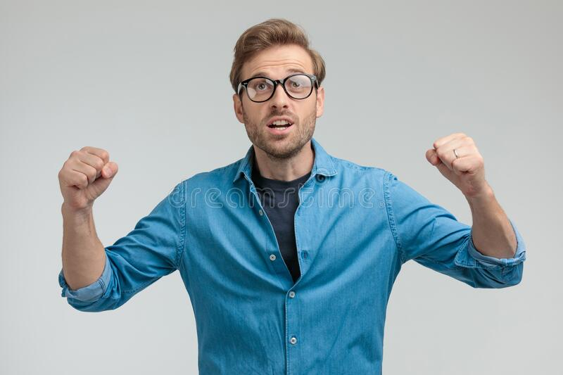 Young casual smart guy holding fists in the air and celebrating stock photography