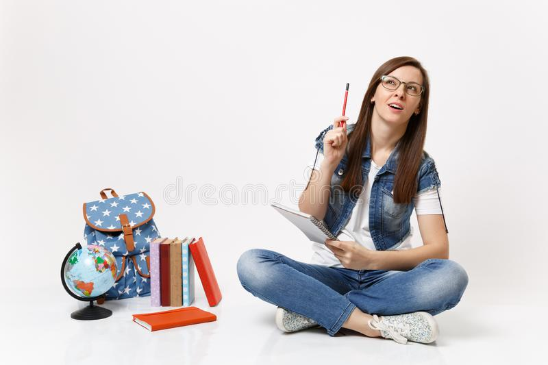 Young casual smart woman student recalling pondering thinking looking up pointing pencil up near globe backpack, school stock photography
