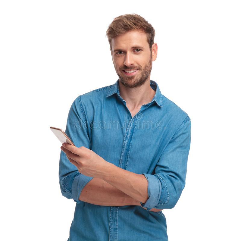Young casual student writes sms message on his mobile phone. On white background stock photography