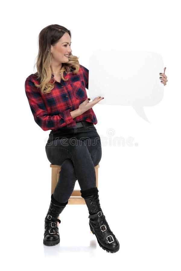 Casual woman sitting with speech bubble on a side royalty free stock photography