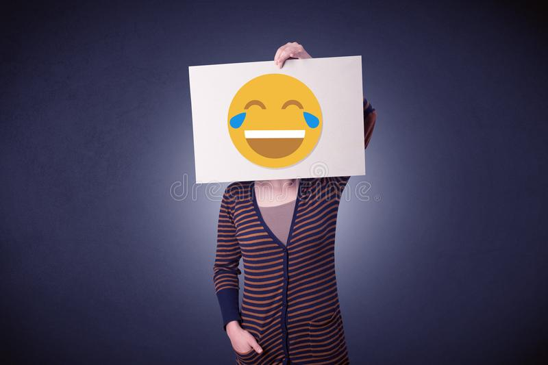 Woman holding paper with laughing emoticon. Young casual woman hiding behind a laughing emoticon on cardboard stock photos