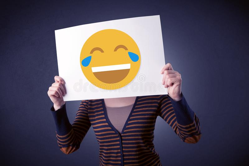 Woman holding paper with laughing emoticon. Young casual woman hiding behind a laughing emoticon on cardboard stock images