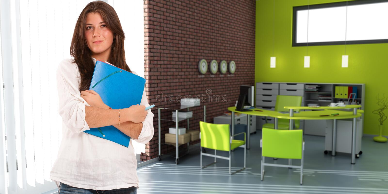 Young casual woman in an office. Young casually dressed woman carrying a folder in an office interior stock photography