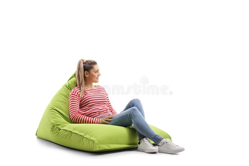 Young casual woman sitting on a bean bag stock photo