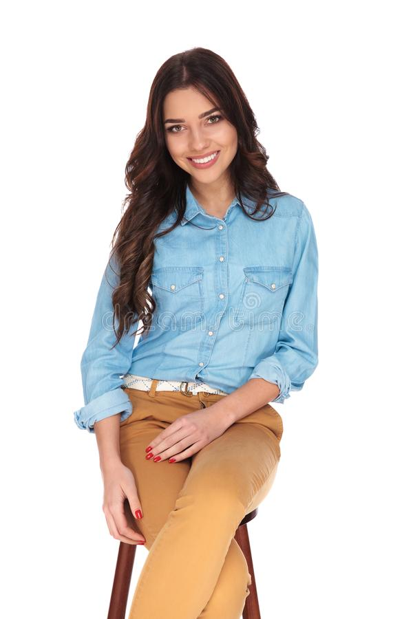 Young casual woman is sitting on chair and laughs royalty free stock photo