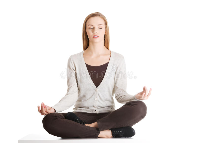 Young casual woman sitting and doing yoga. stock image
