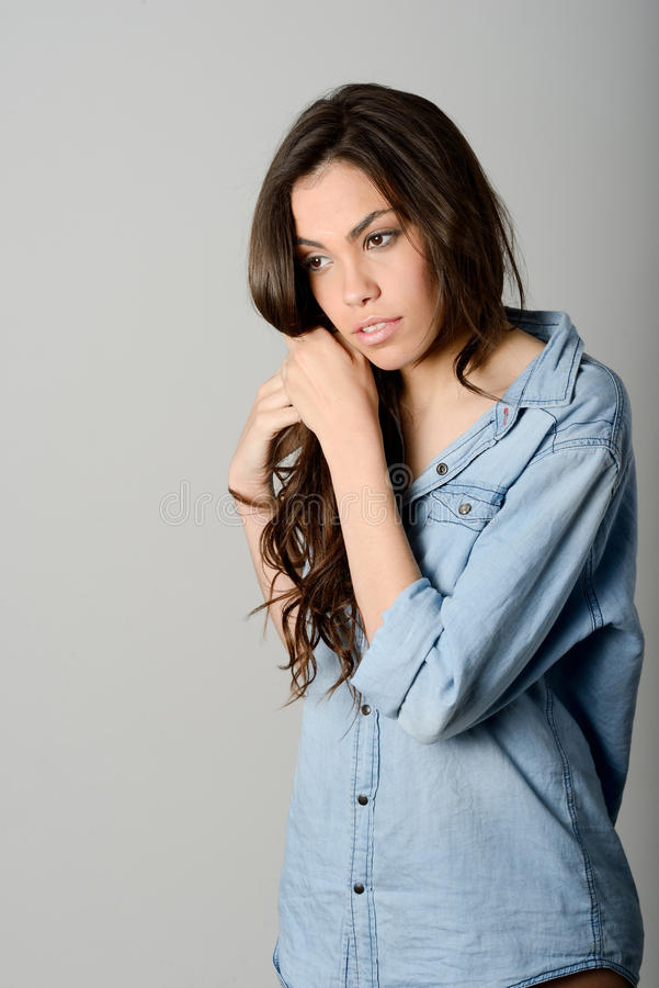 Young casual woman style over gray background. Studio portrait stock image